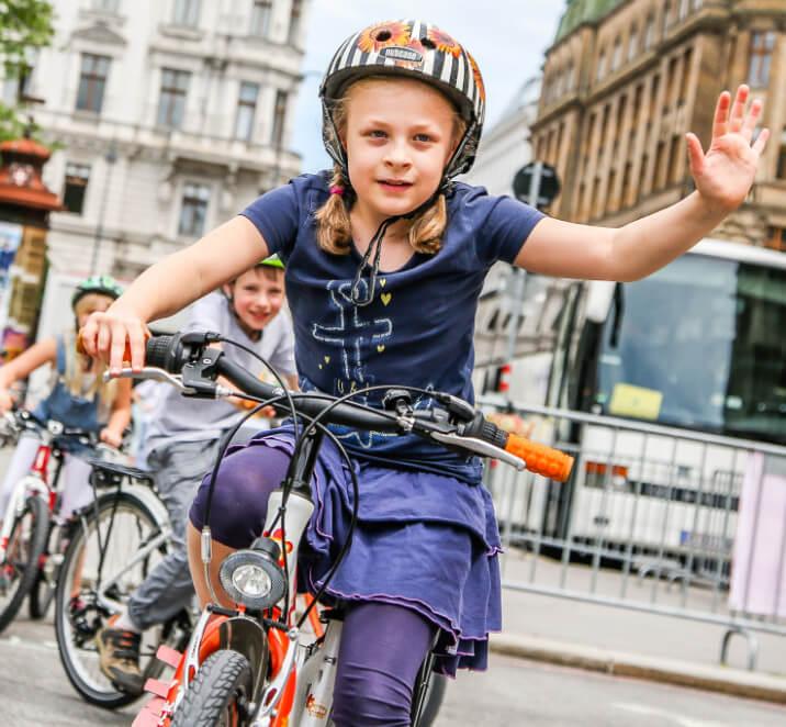 Kind auf Fahrrad hebt die Hand